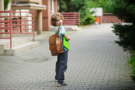 beginning school year: Little schoolboy stand on a schoolyard. He looks in the camera with a serious look. Behind shoulders at the boy a school backpack. Stock Photo