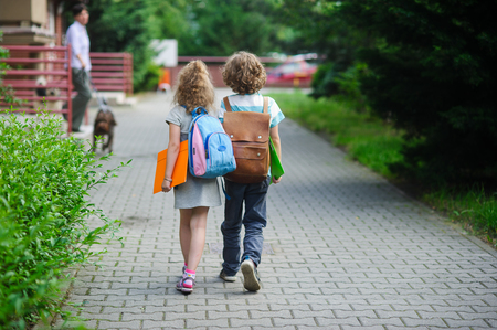 beginning school year: Two pupils of primary school go hand in hand. Boy and girl with school bags behind the back. Beginning of school lessons. Warm day of fall. Stock Photo