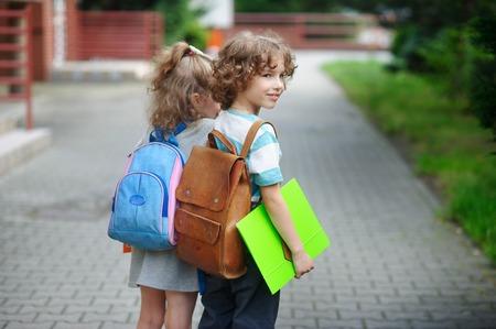manos unidas: Dos pequeños alumno de la escuela primaria, niño y niña, que ensambla las manos. El muchacho con una sonrisa se ve en alguna parte. Cuesta en un medio giro a la cámara.