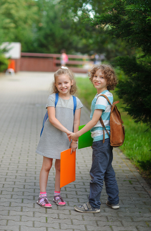 beginning school year: Boy and girl - pupils of elementary school. Beginning of academic year. Children hold hands and smile. Warm day of an early autumn.
