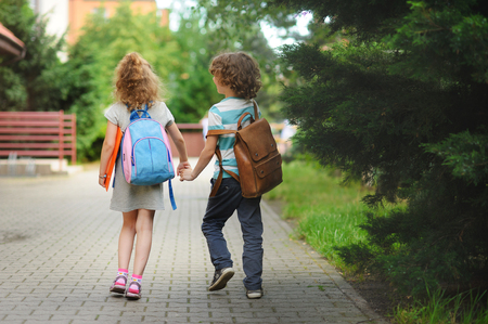 beginning school year: Young students, boy and girl, going to school. They hold hands. They hold hands. Children behind shoulders have satchels. Warm day in an early autumn.