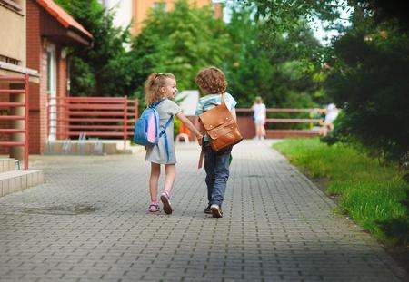 Boy und Gerlie zur Schule gehen sich die Hände. Warm September Tag. Gute Laune. Hinter Rücken an Schulranzen Kinder. Das kleine Mädchen lacht.