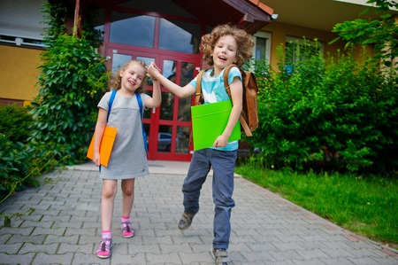 beginning school year: Two pupils of elementary school, boy and girl, on a schoolyard. They play pranks. Children have a good mood. They laugh. Stock Photo