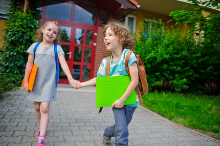 pranks: Two pupils of elementary school, boy and girl, on a schoolyard. They play pranks. Children have a good mood. They laugh. Stock Photo