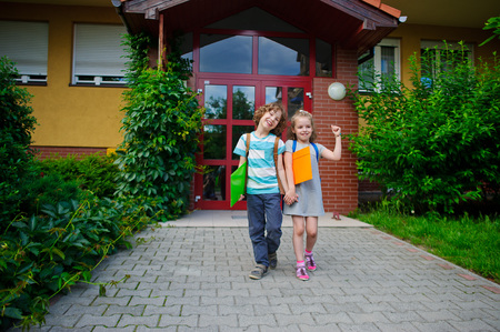 manos unidas: Niño y niña van en un patio de la escuela que tienen manos unidas. Son alumnos de la escuela primaria. Amigos de la escuela. Para los niños es alegre. Día soleado.