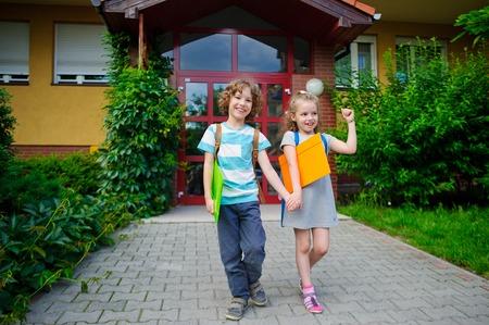 manos unidas: Gerl chico y van a la escuela tienen manos unidas. día de septiembre caliente. Buen humor. En las caras de una sonrisa.