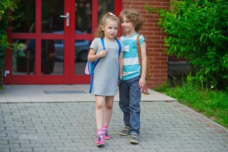 manos unidas: Chico e ir a la escuela que unieron sus manos. día de septiembre caliente. Buen humor. estudiantes de la escuela acerca de algo de conversación. En las caras bonitas sonrisas.
