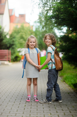 Boy and girl with schoolbags hold hands. Children go to school. They have a good mood. Warm summer day. School students with a smile look in the camera.