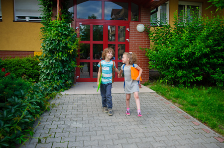 beginning school year: Boy and gerlie go to school having joined hands. Warm September day. Good mood. On faces of a smile. Stock Photo