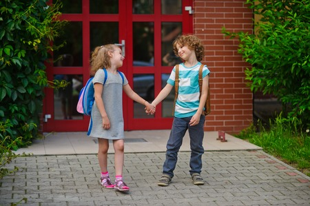 schoolyard: Little school students go on a schoolyard holding hands. Children with a smile look at each other. Boy and girl. Schoolmates. Stock Photo
