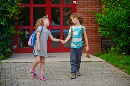 beginning school year: Little school students go on a schoolyard holding hands. Children with a smile look at each other. Boy and girl. Schoolmates. Stock Photo