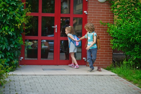 schoolmate: Two pupils of elementary school on a schoolyard. The boy holds the schoolmate by a hand. And the little girl with curiosity looks at a glass door of school. Stock Photo