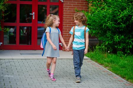 manos unidas: Chico e ir a la escuela que unieron sus manos. d�a de septiembre caliente. Buen humor. estudiantes de la escuela acerca de algo de conversaci�n.