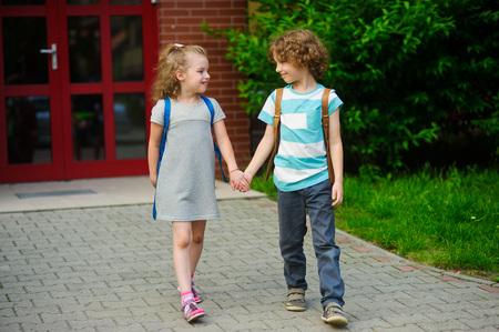 manos unidas: Pequeños alumnos en una escuela. El niño y la niña van a ensamblar las manos. Detrás de los hombros de los estudiantes de la escuela mochilas. Los niños miran el uno al otro y sonrisa. De vuelta a la escuela.