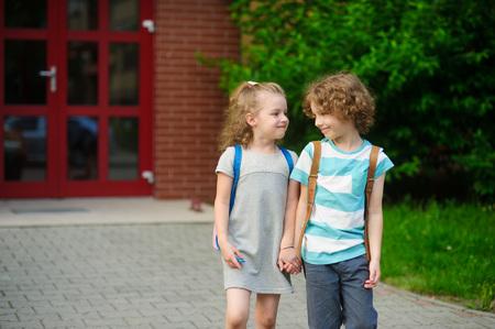 manos unidas: Los pequeños compañeros de clase en una escuela. El niño y la niña van a ensamblar las manos. Detrás de los hombros de los estudiantes de la escuela mochilas. Los niños miran el uno al otro y sonrisa. Foto de archivo