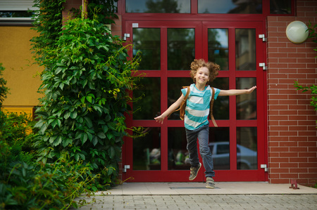 The carefree first grader rejoices to the beginning of summer vacation. He runs out from doors of school. As if flies. On a face of the school student expression of happiness.