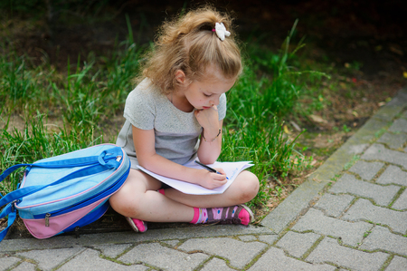 first year student: The little schoolgirl sits having crossed legs on a grass and something writes to a notebook. Girlie has a thoughtful look. Near the girl her satchel lies. Back to school. Stock Photo
