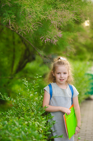 first year student: The little schoolgirl stand on background park vegetation. The girlie has a nice face and a fair hair. She looks in the camera and smiles. Behind shoulders a satchel, in hands - bright folders.