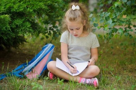 girlie: Schoolgirl of elementary school sits having crossed legs under a tree and does homework. Girlie has a thoughtful look. Near the girl her satchel lies. Back to school.