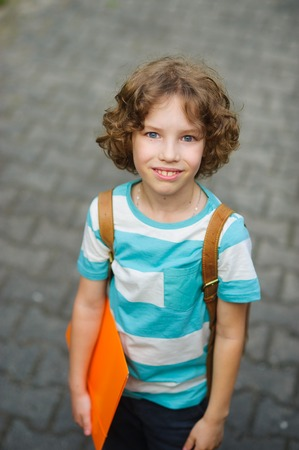 schoolkid: The schoolkid stand on a schoolyard and smiles. The boy has a nice face, a fair hair, an open look. It has behind shoulders a satchel. Orange folder in hands. Stock Photo