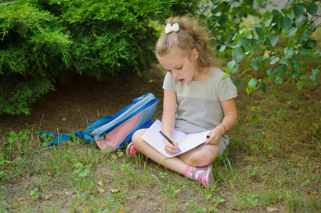 satchel: First grader sits having crossed legs under a tree and does homework. Girlie has a thoughtful look. Near the girl her satchel lies. Back to school.
