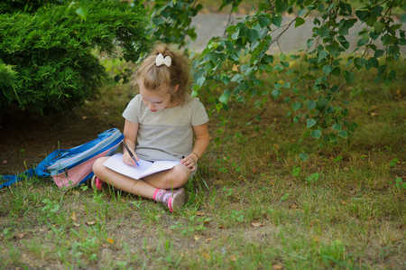 satchel: Little schoolgirl sits having crossed legs under a tree and something diligently writes in the notebook. Girlie has a thoughtful look. Near the girl her satchel lies. Back to school. Stock Photo