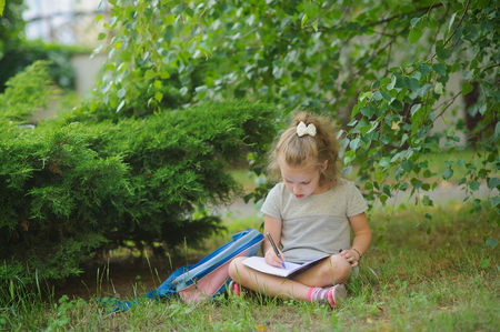 satchel: Little schoolgirl sits having crossed legs under a tree and does homework. Girlie has a thoughtful look. Near the girl her satchel lies. Back to school. Stock Photo
