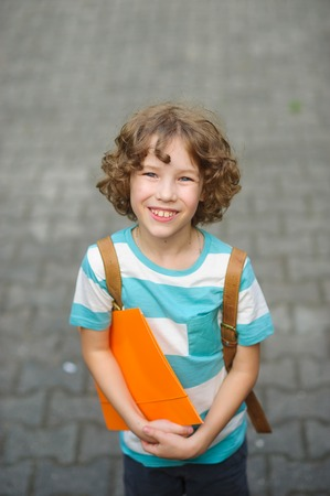 satchel: The fair-haired curly schoolboy looks in the camera and smiles. The boy has a nice face, a fair hair, an open look. It has behind shoulders a satchel. Orange folder in hands .
