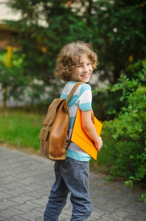 beginning school year: The pupil with a school backpack behind the back. The school student stand in a half-turn to the camera. He looks in a camera and smiles. In hands - the yellow folder.
