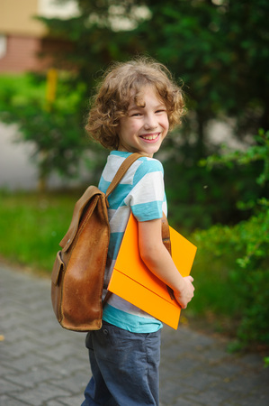 beginning school year: The pupil of elementary school on a schoolyard. The school student costs in a half-turn to the camera and smiles. Behind shoulders at the boy a satchel, in hands - the bright folder. Stock Photo