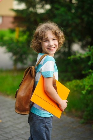 satchel: Cheerful school student on a schoolyard. The curly boy with a nice face. Behind the school students shoulders a satchel. Stock Photo