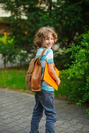 beginning school year: The schoolboy stand in a half-turn to the camera and joyfully smiles. The boy has a nice face, a fair hair, an open look. It has behind shoulders a satchel. Yellow folder In hands.