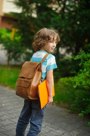 beginning school year: Little schoolboy with a school backpack behind the back. The school student stand in a half-turn to the camera. He looks in a camera and smiles. In hands - the yellow folder.