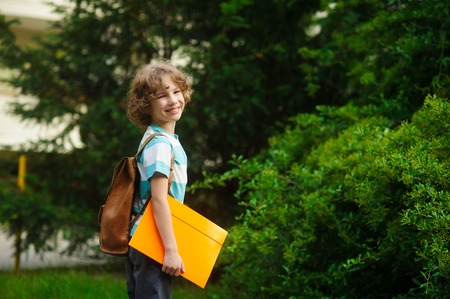 satchel: The pupil of elementary school on a schoolyard. The school student stand in a half-turn to the camera and smiles. Behind shoulders at the boy a satchel, in hands - the bright folder.