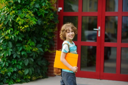 satchel: The little pupil on a schoolyard. The school student with a smile looks in the camera. Behind shoulders at the pupil a satchel, in hands the bright folder. Back to school.