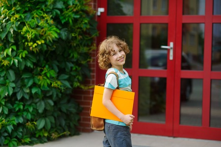 satchel: Cheerful pupil coming to the school door. Behind shoulders at the pupil a satchel, in hands the bright folder. The schoolboy with a smile looks in a camera. Back to school.