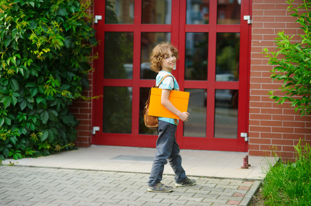 scholastic: Cheerful first grader coming to the school door. Behind shoulders at the pupil a satchel, in hands the bright folder. The schoolboy with a smile looks in a camera. Back to school.