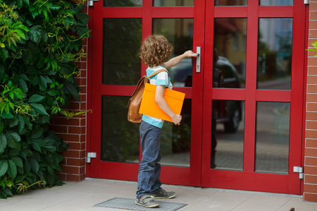 The little first grader opens a door of school. Behind shoulders at the pupil a school backpack, in hands the bright folder. Back to school. Stock Photo