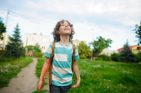 beginning school year: The school student comes back from school in good mood. The boy goes on a footpath. He has raised eyes to the sky and smiles. Behind shoulders at the pupil a satchel.
