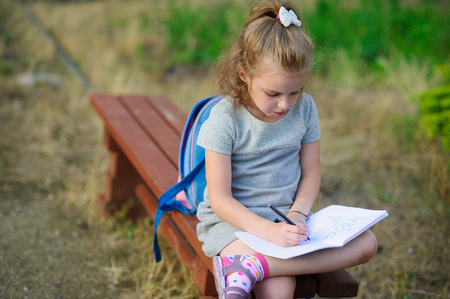 girlie: Little school miss sits having crossed legs on a park bench and something diligently writes in the notebook. Girlie has a thoughtful look. Behind the back the school backpack lies. Back to school.