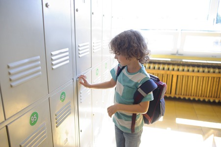 first year student: Little schoolboy standing near lockers in school corridor and opens his drawer. Behind the boys school backpack.