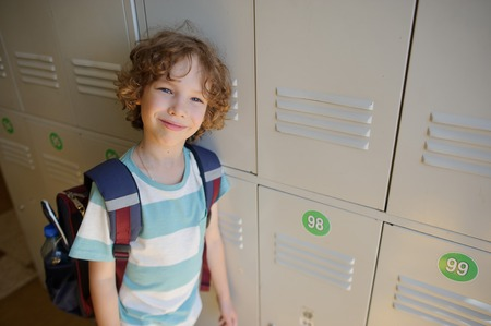 wistful: Little schoolboy standing near lockers in school hallway. He leaned against the locker. The boy with a wistful smile, looking at the camera.