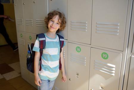 学校の廊下でロッカーの近くに立って小さな少年。ロッカーに寄りかかった。哀愁を帯びた笑みを浮かべてカメラを見て少年。 写真素材
