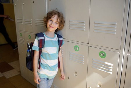 Little schoolboy standing near lockers in school hallway. He leaned against the locker. The boy with a wistful smile, looking at the camera.