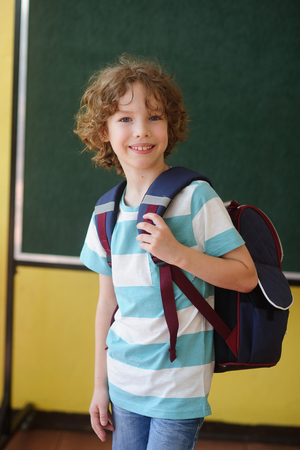 first year student: The pupil of elementary school stands in the class near a board. Behind shoulders at it a school backpack. The school student looks in the camera and smiles. Back to school.
