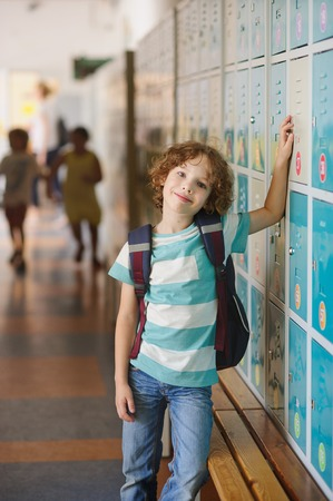 first year student: Little learner standing near lockers in school hallway. He put his hand on my locker. The boy with a wistful smile, looking at the camera. Stock Photo