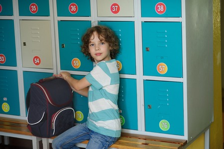 first year student: Little schoolboy sitting on the bench near the lockers. His backpack is nearby. The boy looks into the camera with a serious expression. He had curly blond hair and a nice face.