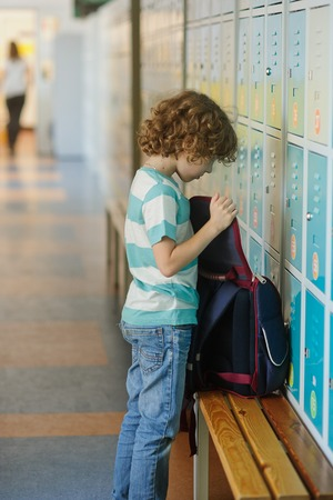 scholastic: Little schoolboy standing near lockers in school hallway. He put the backpack on the bench and something its looking for.