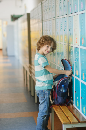Little schoolboy standing near lockers in school hallway. He put the backpack on the bench and something its looking for.