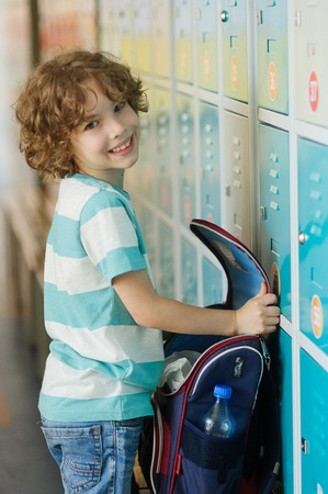 beginning school year: The primary school students standing near lockers in school hallway. He put the backpack on the bench and something its looking for. Boy smiling.